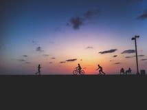Aktywni ludzie są biegający i jeździć na rowerze na zmierzchu Obrazy Royalty Free