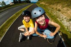 Aktywni młodzi ludzie - rollerblading, jeździć na deskorolce Zdjęcie Stock