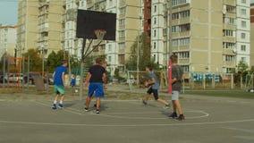 Aktywni nastolatkowie bawić się streetball grę outdoors zbiory
