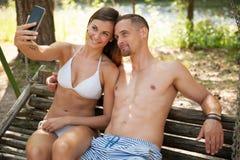 Aktywni potomstwa dobierają się brać selfie na ławce w parkowej pobliskiej rzece zdjęcia royalty free