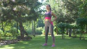 Aktywny żeński robi rozciągania ćwiczenie na trawie zdjęcie wideo