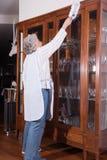Aktywny żeński senior czyści meble Zdjęcia Royalty Free