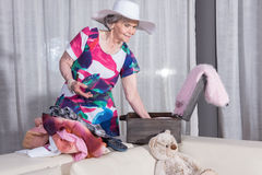 Aktywny żeński senior pakuje rocznik walizkę dla wakacje Fotografia Stock