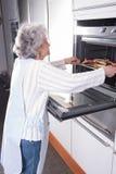 Aktywny żeński senior przy piekarnikiem obraz stock