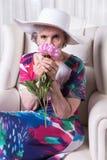 Aktywny żeński senior wącha kwiatu Obrazy Stock