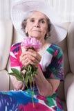 Aktywny żeński senior wącha kwiatu Zdjęcia Royalty Free