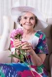 Aktywny żeński senior wącha kwiatu Obrazy Royalty Free