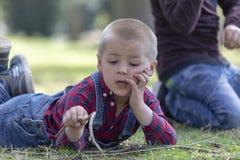 Aktywny chłopiec wskazywać drewniany wtyka w górę podczas gdy chodzący w wiosna parku, dziecko chłopiec ma zabawę bawić się plene zdjęcie royalty free