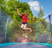 Aktywny dziewczyny doskakiwanie na trampoline outdoors obraz royalty free