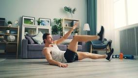 Aktywny facet ćwiczy robić sportom kłama na podłogowym dźwiganiu w domu iść na piechotę i ręki zbiory
