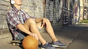 Aktywny mężczyzna obsiadanie na deskorolka, bawić się piłkę i słuchanie muzyka w słuchawki zdjęcia royalty free