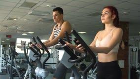 Aktywny młody człowiek i kobieta używa elliptical maszynę zbiory wideo