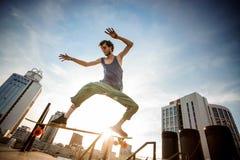 Aktywny młody deskorolkarz skacze na pokładzie miasto budynku przeciw zdjęcia stock