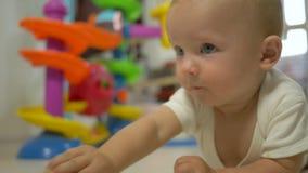 Aktywny niemowlak bawić się z zabawkami i kraulami na podłogowym zakończeniu zdjęcie wideo