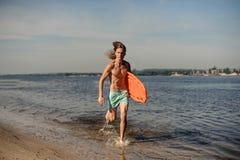 Aktywny seksowny plażowy ratownika bieg wzdłuż brzeg rzeki z li Obraz Stock