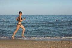 Aktywny sporty kobieta bieg wzdłuż ocean kipieli wodnym basenem utrzymywać napad i zdrowie Zmierzchu piaska plaży czarny tło z obraz royalty free