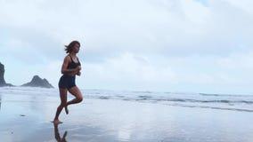 Aktywny sporty kobieta bieg wzdłuż ocean kipieli wodnym basenem utrzymywać napad i zdrowie Zmierzchu piaska plaży czarny tło z zbiory
