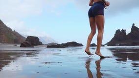 Aktywny sporty kobieta bieg wzdłuż ocean kipieli wodnym basenem utrzymywać napad i zdrowie Zmierzchu piaska plaży czarny tło z zbiory wideo