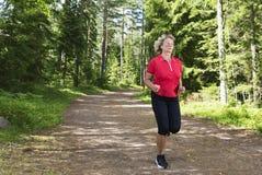 Aktywny starszy kobieta bieg przy lasowym jogging śladem fotografia royalty free