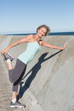 Aktywny starszy kobiety rozciąganie na molu fotografia royalty free