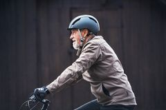 Aktywny starszy mężczyzna jeździć na rowerze outdoors againts zmroku tło z roweru hełmem zdjęcie stock