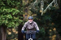 Aktywny starszy mężczyzna jeździć na rowerze outdoors na drodze w naturze z electrobike zdjęcie stock
