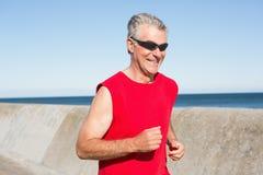 Aktywny starszy mężczyzna jogging na molu Obrazy Stock