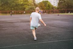 Aktywny styl życia w nowożytnym mieście - sporty obsługują bawić się z piłki nożnej piłką przy stadium obrazy stock