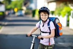 Aktywny szkoły dzieciaka chłopiec w zbawczego hełma jazdie z jego hulajnoga w mieście z plecakiem na słonecznym dniu Szczęśliwy d obrazy stock