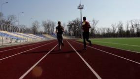 Aktywnych potomstw dziewczyny chłopiec pary dysponowany atrakcyjny bieg jogging outside dużego stadium pracujący out outdoors tre zbiory