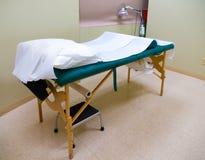 Akupunktur, massagetabell & värmelampa i behandlingrum Arkivfoton