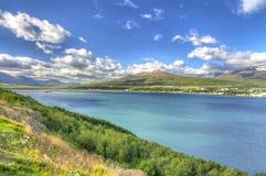 Akureyri beskådade från den östliga kusten av Eyjafjordur royaltyfria foton