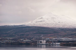Akureyri City Cityscape with Mountain, Cloudy Sky and River. Iceland. Stock Photos