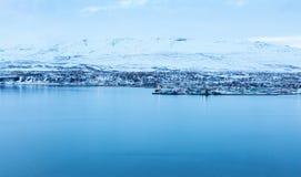 Akureyri, with Hlidarfjall behind. Akureyri, with Hlidarfjall behind, viewed from the eastern shore of Eyjafjordurat dusk in winter, northern Iceland Stock Images