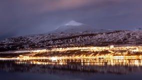Akureyri Island stadsljus under blåa timmar med en bakgrund av isberg royaltyfria bilder
