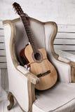 Akustikgitarre auf einem alten Lehnsessel lizenzfreie stockbilder