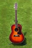 Akustikgitarre auf Hintergrund des grünen Grases. Stockfotos