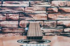 Akustikgitarre auf Wandhintergrund des roten Backsteins lizenzfreie stockbilder