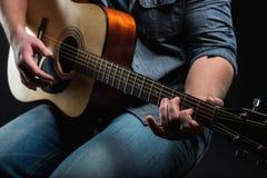 Akustikgitarre in den Händen des Kerls gestalten im Allgemeinen Lizenzfreie Stockfotos