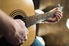 Akustikgitarre in den Händen des Kerls gestalten im Allgemeinen Lizenzfreies Stockbild