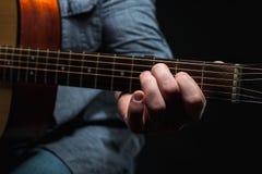 Akustikgitarre in den Händen des Kerls gestalten im Allgemeinen Stockfotografie
