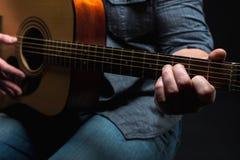 Akustikgitarre in den Händen des Kerls gestalten im Allgemeinen Stockfoto