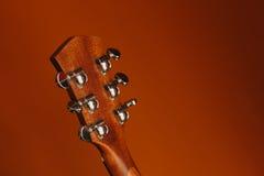 Akustikgitarre der Sechsschnur auf einem roten Hintergrund Lizenzfreies Stockfoto