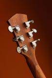 Akustikgitarre der Sechsschnur auf einem roten Hintergrund Stockfotografie