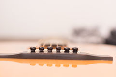 Akustikgitarre, die gegen einen hölzernen Hintergrund mit Kopien-SP stillsteht lizenzfreies stockbild