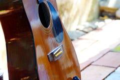 Akustikgitarre, die im Garten stillsteht stockfotografie