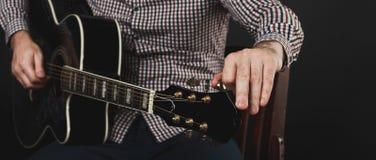 Akustikgitarre, die nah abstimmt und oben spielt Lizenzfreies Stockbild