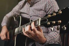 Akustikgitarre, die nah abstimmt und oben spielt Stockbild