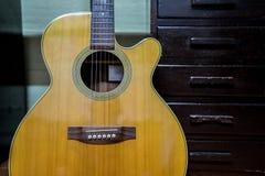 Akustikgitarre gegen einen Fachhintergrund Lizenzfreies Stockfoto