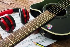 Akustikgitarre, Kopfhörer und Blatt musikalisches noteson die Tabelle Lizenzfreie Stockfotos